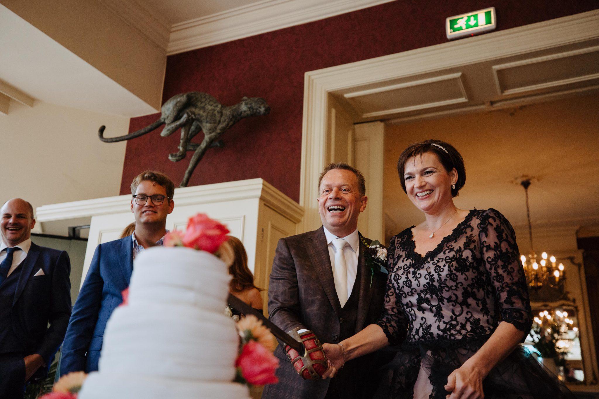 Bruidspaar snijd bruidstaart aan bruidsfotografie