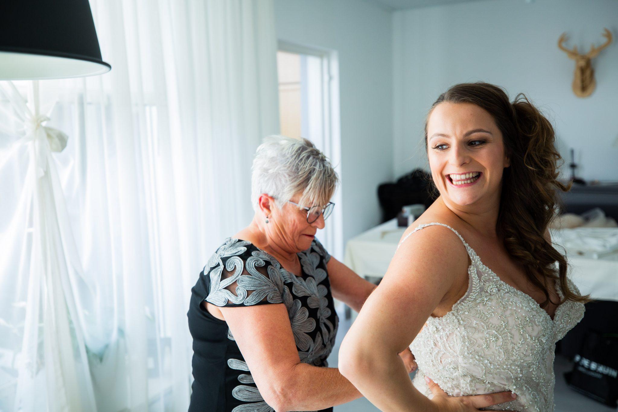 Bruidsfotografie, bruid trekt haar trouwjurk aan