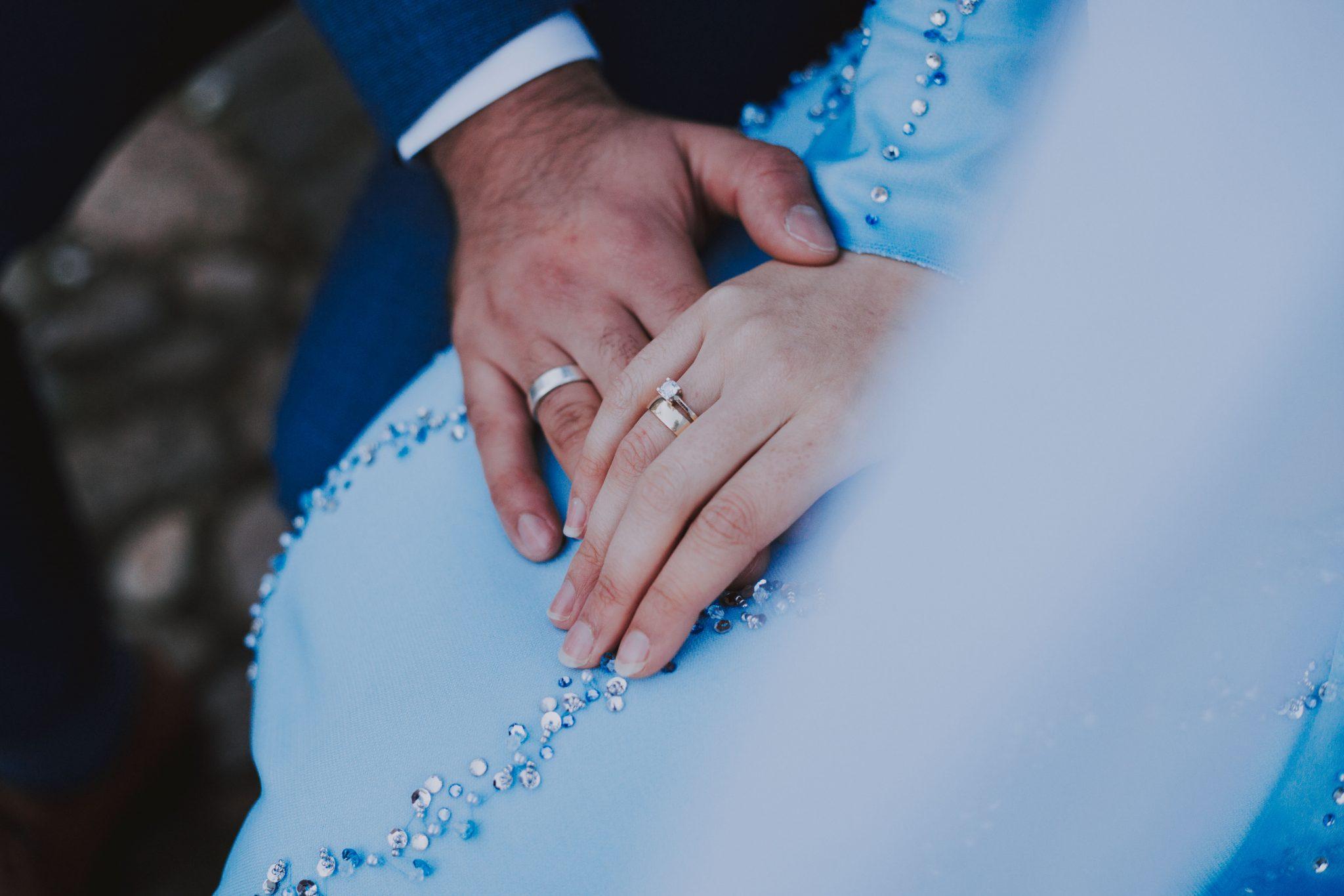 Close up van de trouwringen en verlovingsring van het bruidspaar