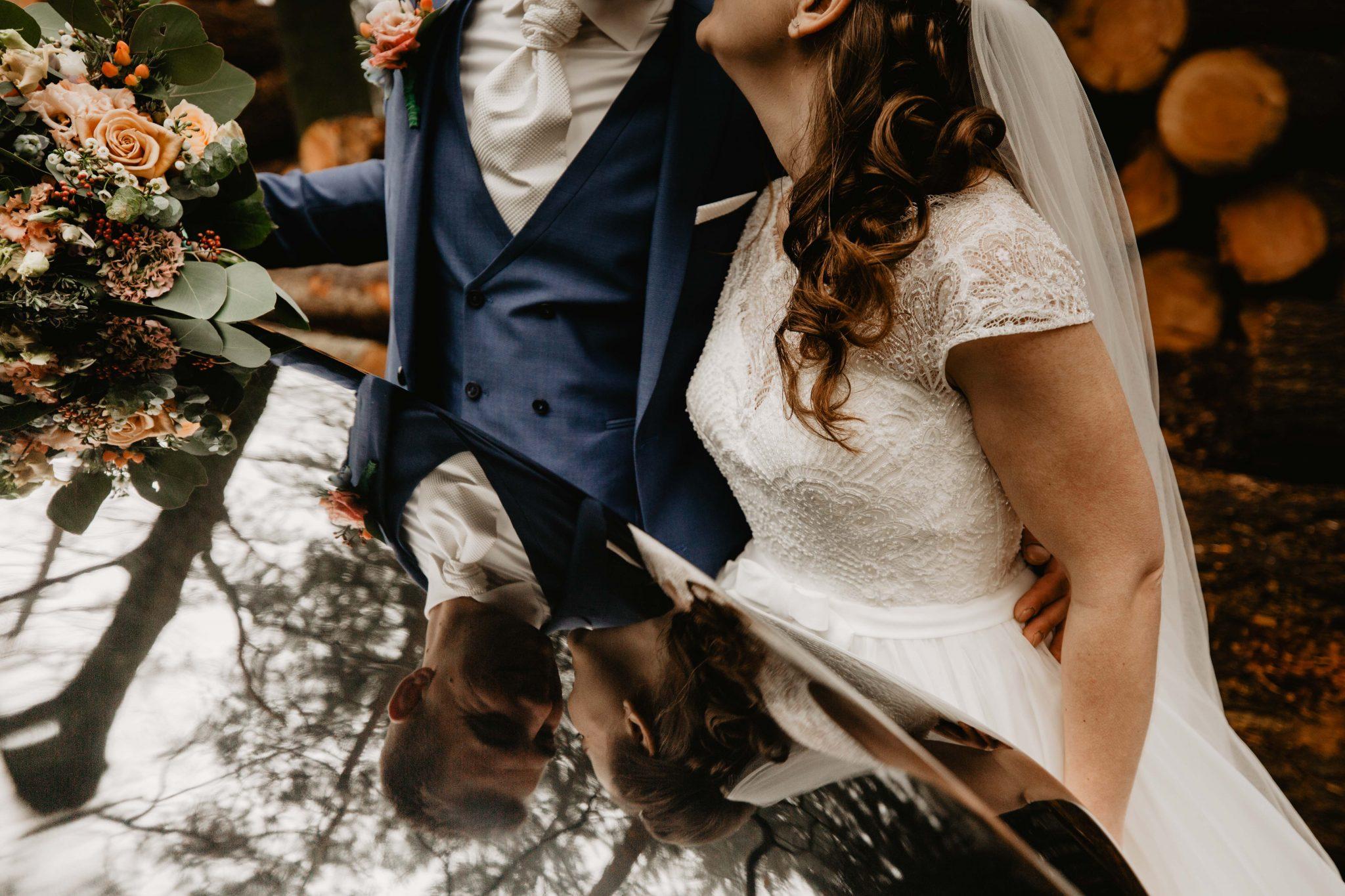 Bruidspaar tijdens fotoreportage bruiloft bij trouwauto