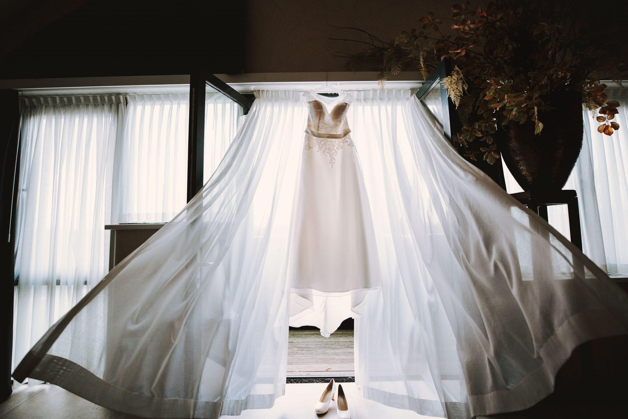 De Trouwjurk van de bruid hangt klaar voor de bruiloft | Bruidsfotograaf