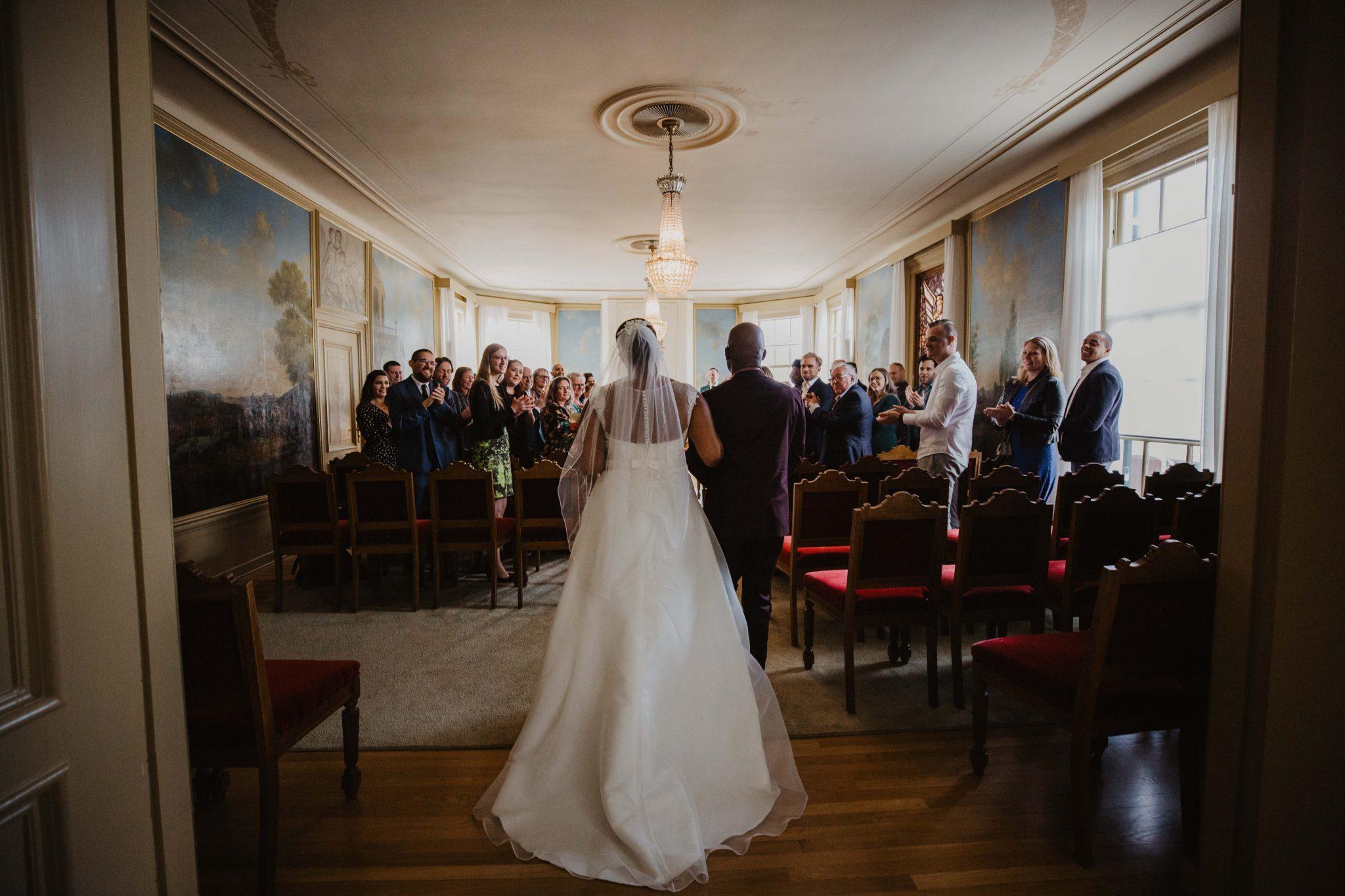 Vader geeft de bruid weg op de ceremonie bij de bruiloft in Nijkerk - Bruidsfotograaf