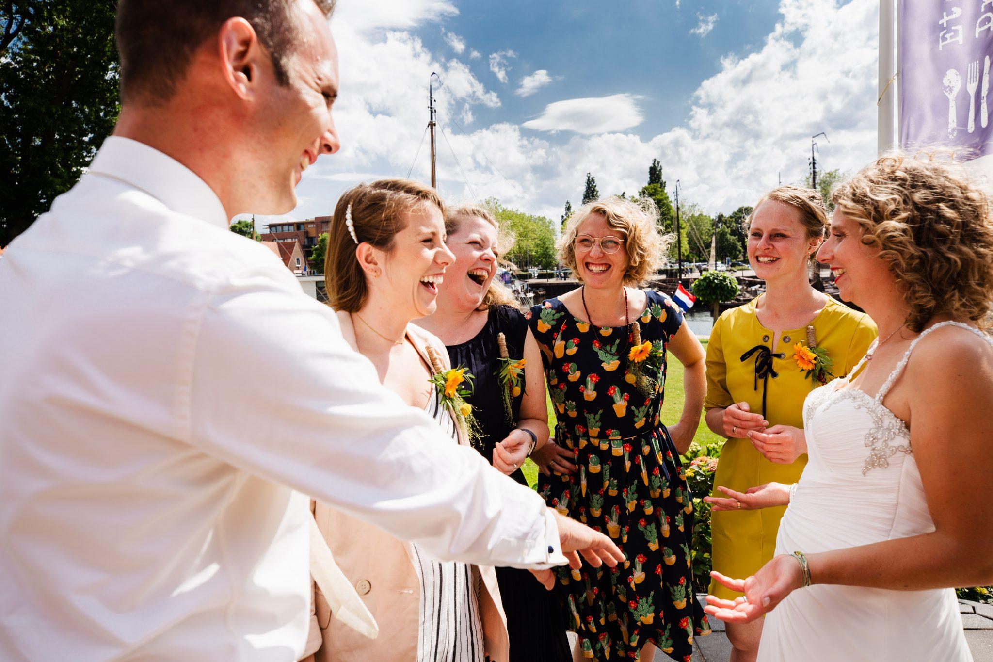Bruidspaar laat trouwringen zien aan vrienden