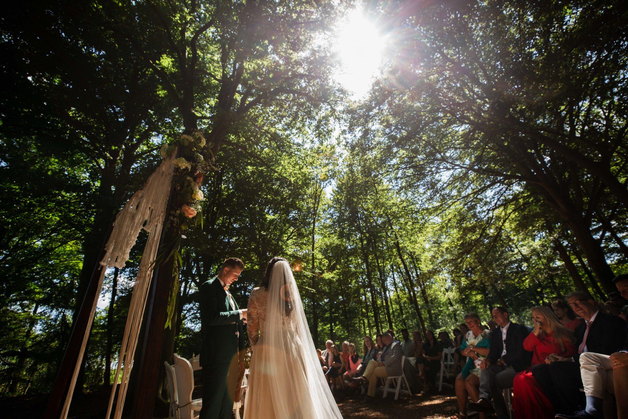 Bruidspaar geeft elkaar de ringen tijdens Bruiloft in het bos van Leusden